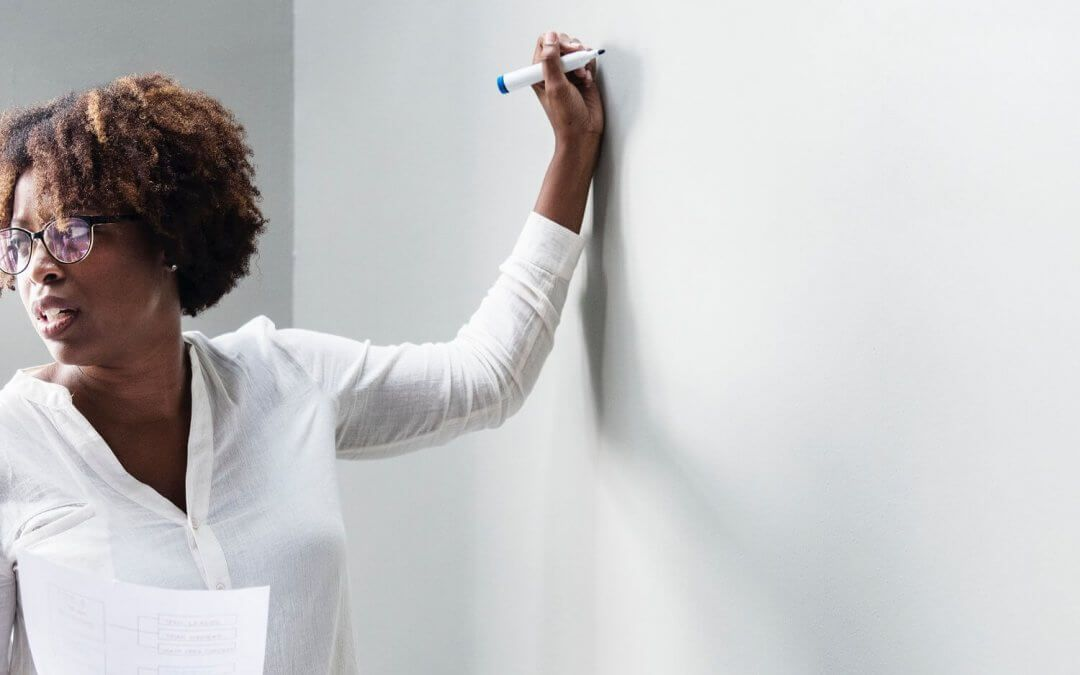 A woman wearing glasses and holding a sheet of paper stands ready to write suggestions on a whiteboard.