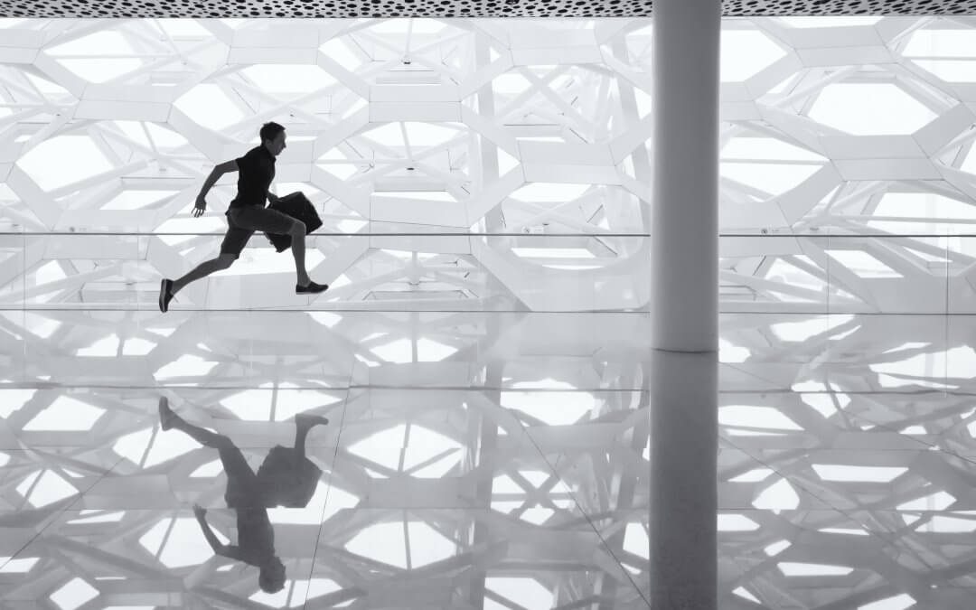 A man with a briefcase runs through a modern building.