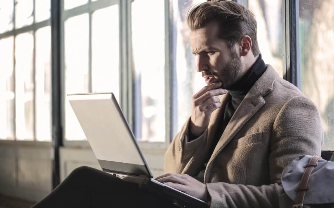 Man in a beige coat stares puzzled at his computer