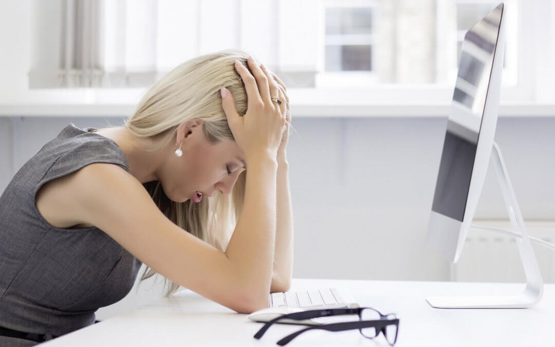 Blonde woman sits with her head in her hands in front of a computer in her office
